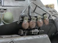 水筒のぶら下げは数少ないディテールアップ箇所のひとつです。細い真鍮線(0.2mm)を火であぶってグニャグニャしてから水筒に巻きつけて車体に縛りつけました。本当にブラブラしています。\r あと、アンテナの後ろの柱にくくりつけてある布袋もスリングを鉛板で作って柱に巻きつけてあります。