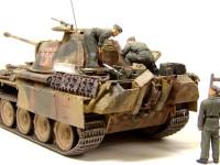 """前回製作した『ドイツ戦車兵エンジン整備セット』の皆さんを乗せてみました。戦車兵は落っこちないように足に真鍮線を埋めて、車体の上に小さな穴を開けて差し込んであります。工具類はおいてあるだけです。下で修理を見守る戦車長は上を見上げるように首の角度を変えてあります。けなげにも自分も黒服の上に作業服を着てきたのですが、部下の方がメカには強いようです。作業服の下から制服のズボンがはみ出ているあたりは、タミヤさん芸が細かいですね。""""><img src=""""../photo/op17/s7.jpg"""" alt=""""エンジン整備中"""