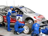 ドライバーはコ・ドライバーの脇に立って打ち合わせ中です。その傍らではタイヤを外してサスペンションの調整にかかっています。