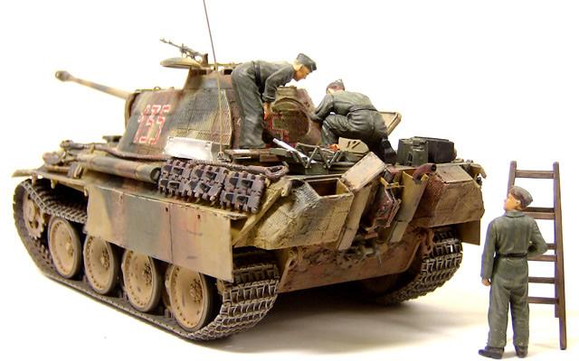 """前回製作した『ドイツ戦車兵エンジン整備セット』の皆さんを乗せてみました。戦車兵は落っこちないように足に真鍮線を埋めて、車体の上に小さな穴を開けて差し込んであります。工具類はおいてあるだけです。下で修理を見守る戦車長は上を見上げるように首の角度を変えてあります。けなげにも自分も黒服の上に作業服を着てきたのですが、部下の方がメカには強いようです。作業服の下から制服のズボンがはみ出ているあたりは、タミヤさん芸が細かいですね。"""">"""